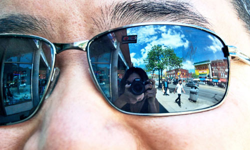 A woman taking a photo on the reflection of a man's sunglasses