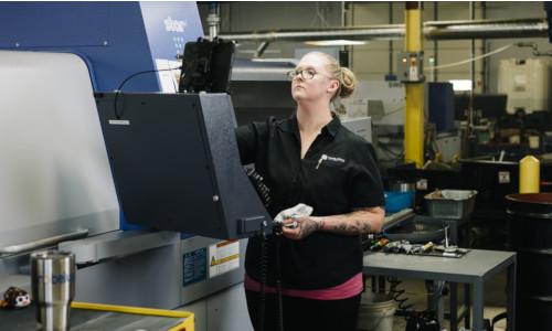 Stacy Czyzewski checks a machine that can manufacture complex aerospace components