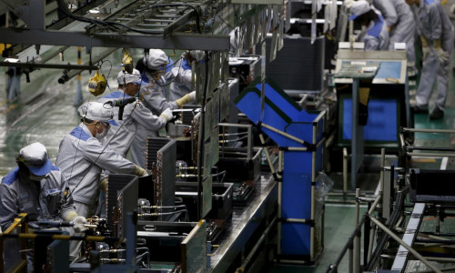 A Daikin Industries Ltd employee works the production line of outdoor air conditioning units