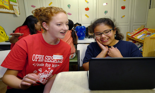 Katherine McPhie, co-founder of the Open Sesame Coding for Kids project, working on computer with a 10-year-old student.