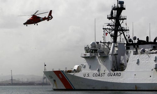 A helicopter lifting off of a Coast Guard vessel.