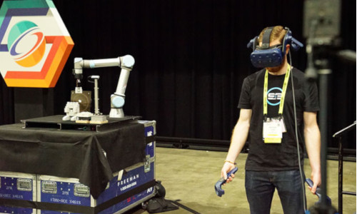 Research engineer wearing a VR headset and using handheld controls