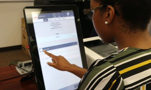 A woman on a voting touchscreen