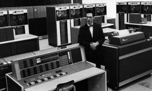 Image of Fernando Corbato standing amongst early computers