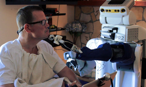 A robot feeding a man