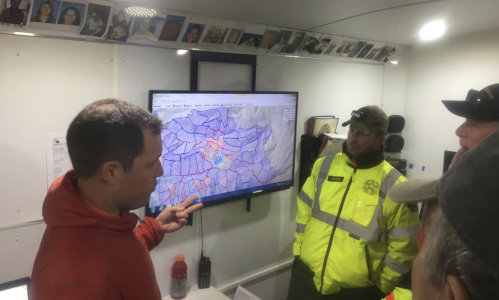 Search and rescue volunteers looking at a screen
