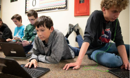 Boys on the floor learning about coding on the computer