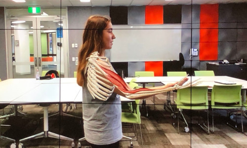 A girl teaching anatomy students about the human body using AR and VR