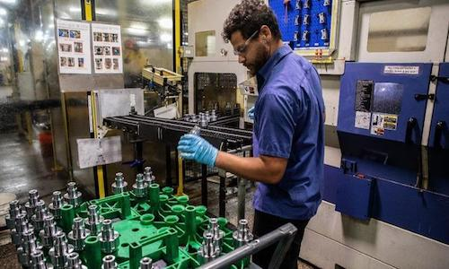 Machine operator inspects automotive parts before feeding them to robots for sorting.