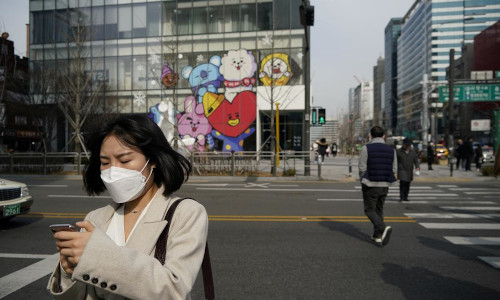 A woman wearing a mask to prevent the coronavirus uses her mobile phone at a shopping district in Seoul, South Korea