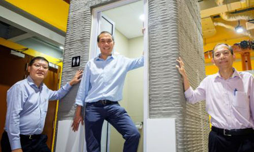 Three men standing with the 3-D printed bathroom unit