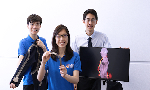 Three researchers holding some of the smart textiles created at the National University of Singapore.