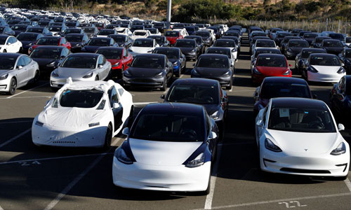 A parking lot of predominantly new Tesla Model 3 electric vehicles