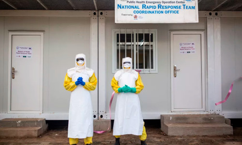 Two people standing side by side in protective suits