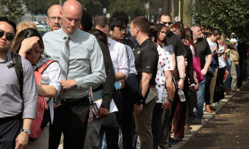 Job seekers wait in line outside a career fair in Chicago hosted by Amazon.com Inc.