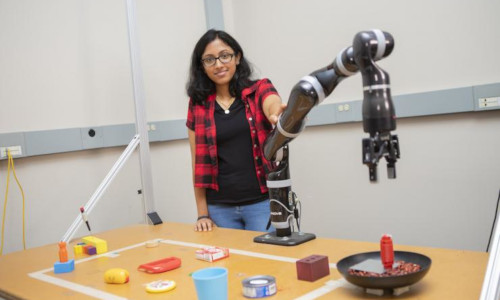 Associate Professor Sonia Chernova holding the robot that's trained to create tools by combining objects