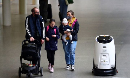 A robot passing by a family