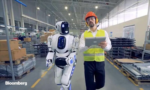 A robot walking next to a man