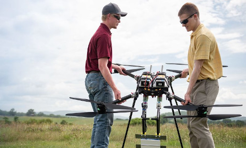Two men carrying a radar-equipped drone out to its launch site during NASA tests of an integrated system designed to enable a drone to autonomously detect and avoid other aircraft