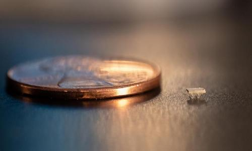 A tiny 3d-printed robot placed next to a penny to illustrates its diminutive dimensions.