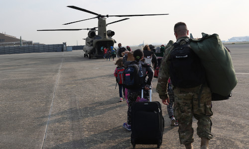 Children and a man heading toward a helicopter