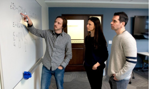 Three individuals from College of Science looking at the board