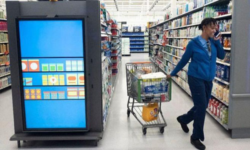 A customer pulling her shopping cart past an information clock at
