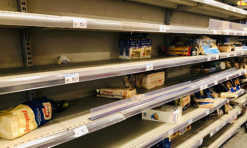 A supermarket with shelves devoid of food and household products during the COVID-19