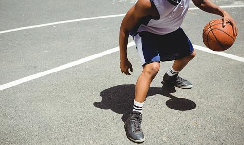 Man dribbling basketball on court