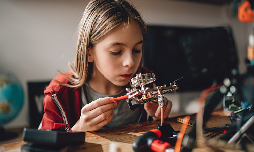 Girl wearing red hoodie looking circuit board throughout magnifying glass
