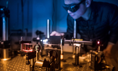 Shengwei Jiang, postdoctoral researcher at Cornell, aligning an optical setup for magneto-optical Kerr rotation microscopy measurements on atomically thin magnets