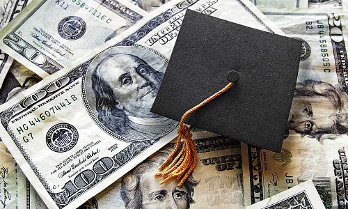 Graduation cap on top of hundred dollar bill