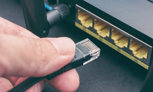 Cable being plugged into a router