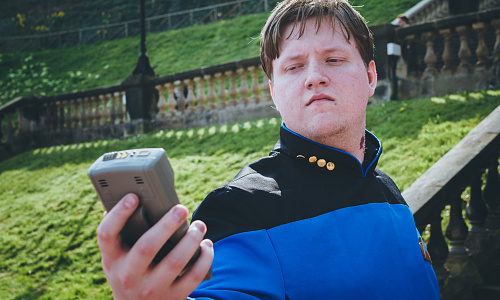 Man dressed in Star Trek costume, holding a tricorder