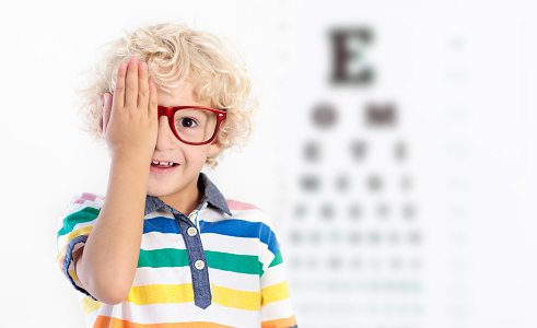 Young boy wearing glasses with vision test in background